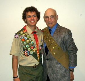 A young Eagle Scout and and Eagle Scout in his 80s, both wearing their sashes.