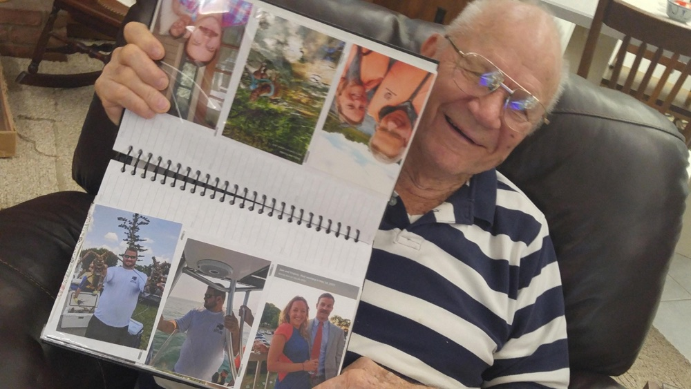 An older man holding printed photos he received from NanaGram