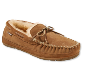 A tan moccasin-style men's slipper with a super soft sherpa interior, rubber bottom, and leather laces.
