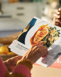 Photo of someone holding a Plated.com recipe card.