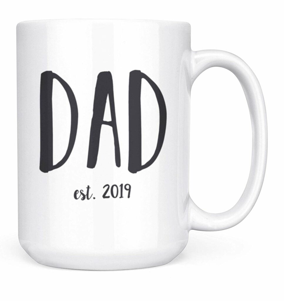 "White mug with large ""DAD"" letters in hand-written copy (like a magic marker) reading below it ""est. 2019"")"