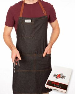 Man in a maroon shirt wearing a blue denim apron with tan straps, holding a grilling tool. Phone in upper left breast pocket.