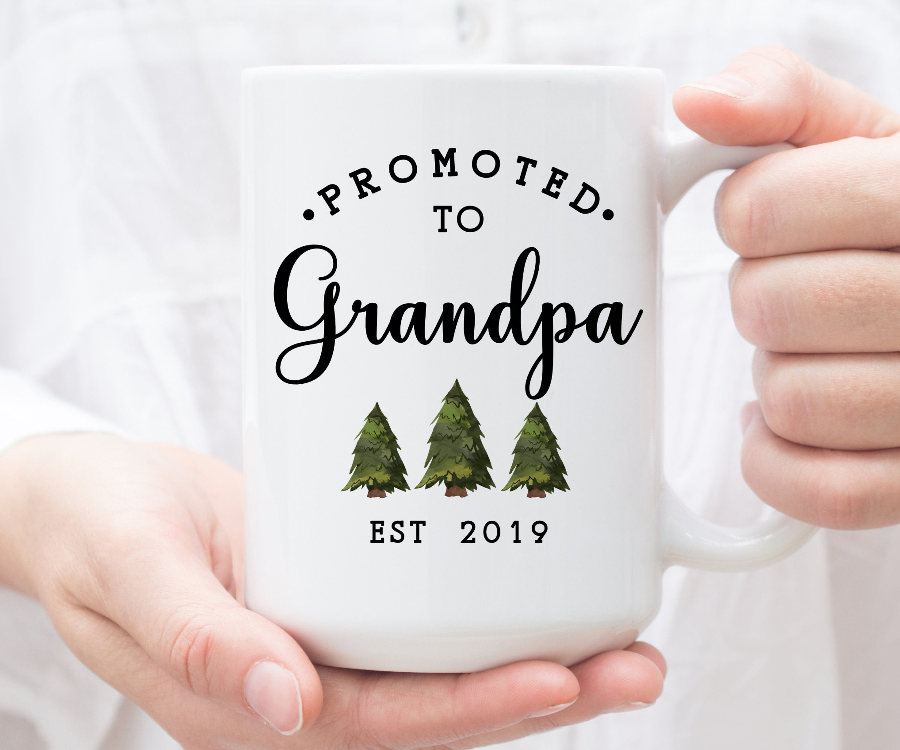 White mug saying: Promoted to Grandpa, est 2019 with 3 small pine trees