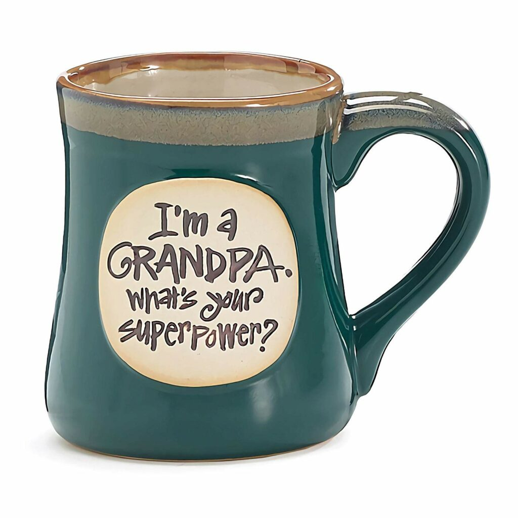 "Clay-type mug with a brown/tan lip and interior and dark green body. Circular area in tan with brown text reading in hand-written style font: ""I'm a Grandpa / What's your superpower?"""