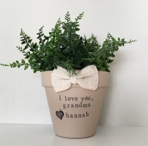 "Potted plant with a bow on it and green plant. Text on the pot reads ""i love you, grandma <3 hannah"""