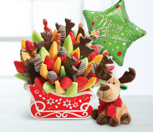 Photo of an edible arrangement Christmas sleigh with a balloon and stuffed reindeer.