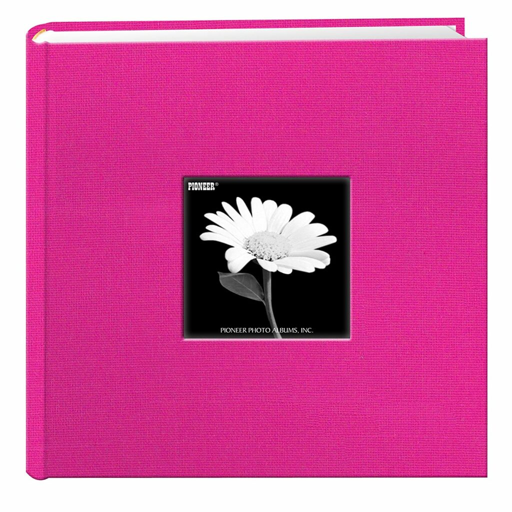 Pink photo album, cloth covered with a small square window on the front displaying a black-and-white photo of a small flower.