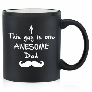 "Black mug with white text. White arrow pointing up with text reading ""This guy is one AWESOME Dad"" with a white mustache icon."