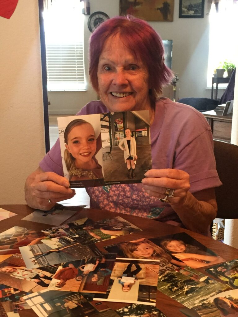 Photo of a grandmother with purple dyed hair, holding photos of her grand daughter.