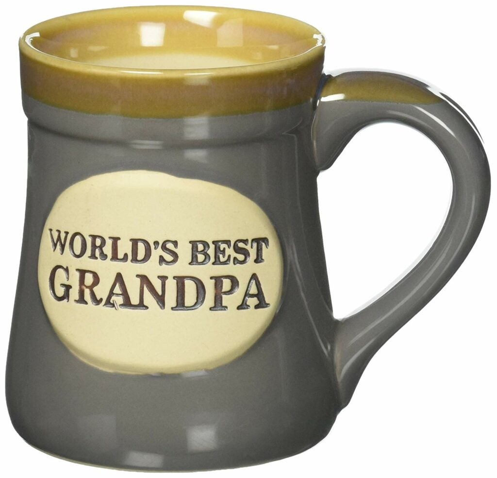 "Shapely coffee mug with a tan lip, lighter tan interior, green/grey body. Circular shape in the middle of the mug in tan with darker tan text reading ""World's Best Grandpa"" with a small rocket icon using a playful font."