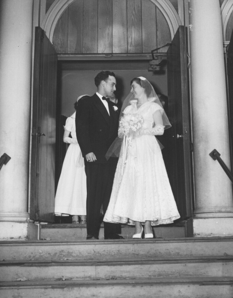 1945 wedding. Groom on the left, bride on the right holding a bouquet of flowers and wearing an ankle-height dress.