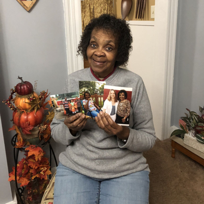 A woman holding 3 printed photos in her kitchen, smiling and wearing a great sweater and blue jeans.