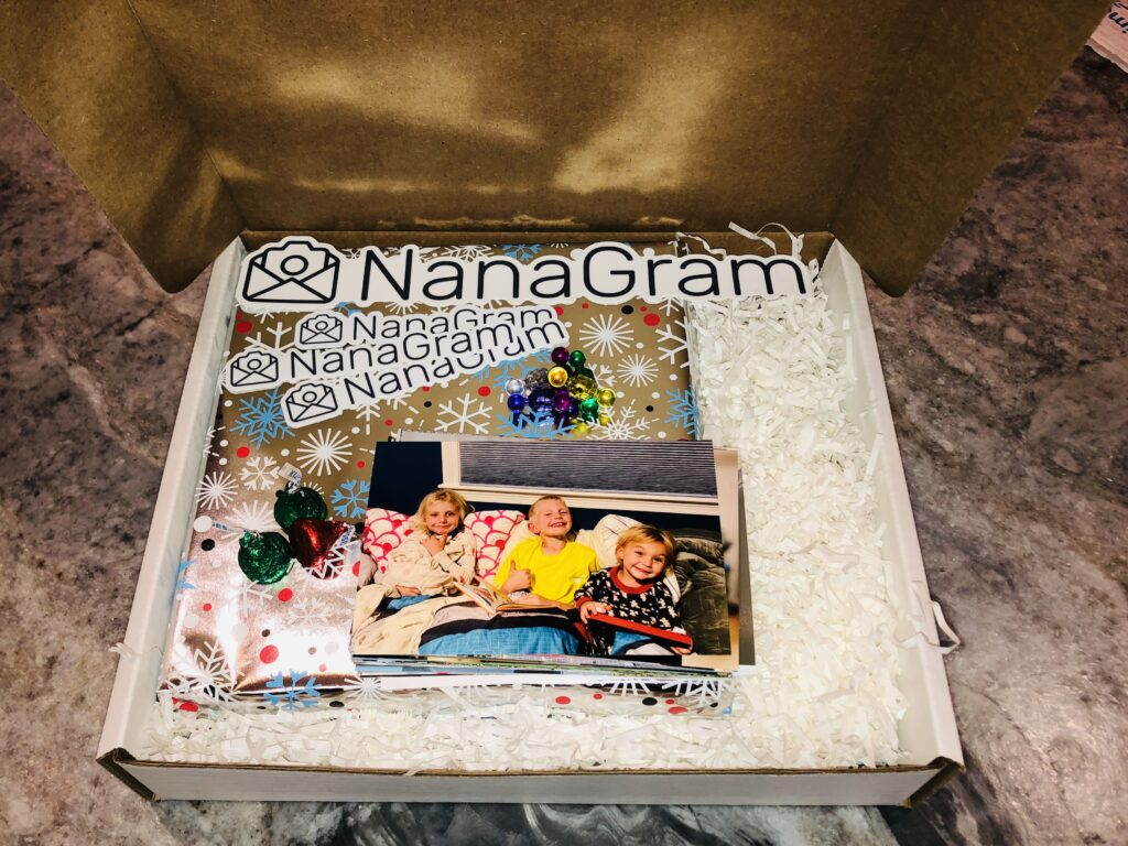Photo album wrapped in shiny holiday/winter paper (snowflakes) with magnetic pins, Hershey Kisses, and printed photos on top. White shredded paper in the box around the photo album and NanaGram stickers in the box as well.