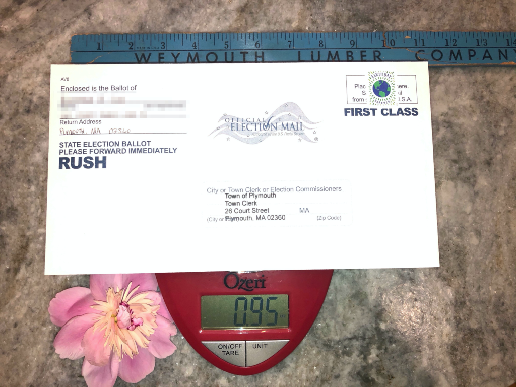 """Photo of an envelope on top of a scale with a ruler above it. The envelope reads """"Official election mail"""" and """"State election ballot please forward immedietely RUSH"""", with the """"to"""" address of the """"City or Town Clerk or Election Commissioners, Town of Plymouth Town Clerk 26 Court St Plymouth MA 02360."""" The ruler above it is blue and reads """"Weymouth Lumber Company"""" showing the envelope is 10.5"""" wide. In the upper right of the envelope is a blue and green stamp showing the earth which says """"Earth Day."""" In the lower left of the image is a pink petunia flower on the countertop next to the envelope. The scale is red and reads 0.95 ounces with two buttons reading """"ON/OFF TARE"""" and """"UNIT."""" The return address of the envelope is blurred out."""