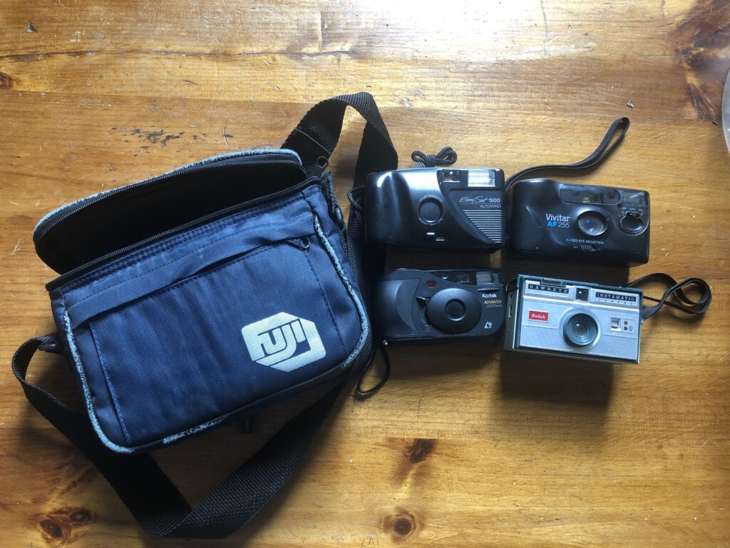 Photo of a blue FUJI camera back, next to it 4 cameras; 3 black and 1 silver.