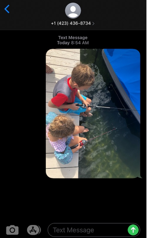 iPhone screen shot showing a photo of two kids fishing, texted to a number 423-436-8734 with no assigned contact