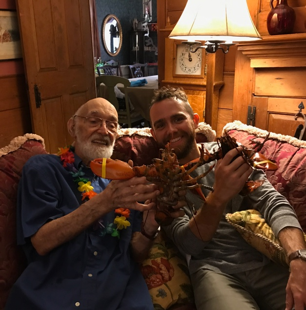 A man in his 90s (Grandpa Cook) and his grandson sitting on a couch holding two live lobsters.