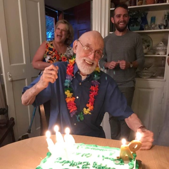 Photo of a man (Grandpa Cook) on his 94th birthday blowing out candles with his grandson (Alex) in the right and his daughter-in-law Janet on the left.