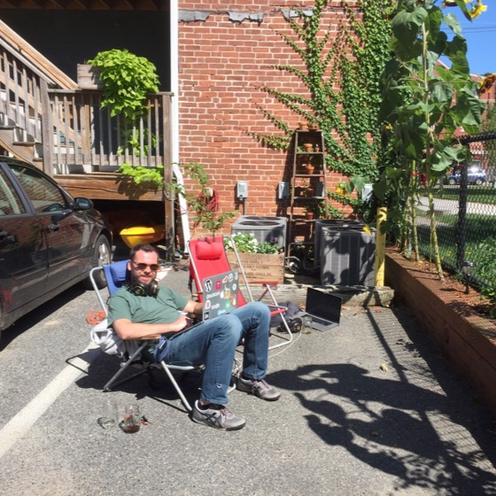 Andy Cook sitting in a parking lot on a lawn chair with his headphones and laoptop, coding NanaGram. An old wooden ladder in the background against a brick building with boston ivy growing up the side.
