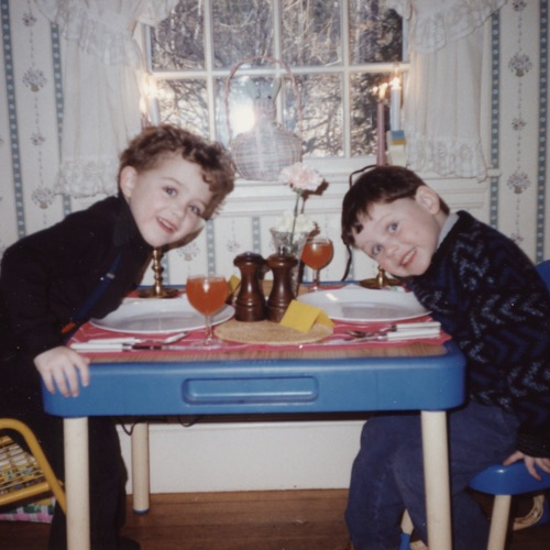 Two boys (Alex and Andy Cook) sitting at a table in the mid 1990s leaning towards each other and smiling with fancy goblin glasses on the table, their own wooden salt and pepper shakers, and a table cloth.